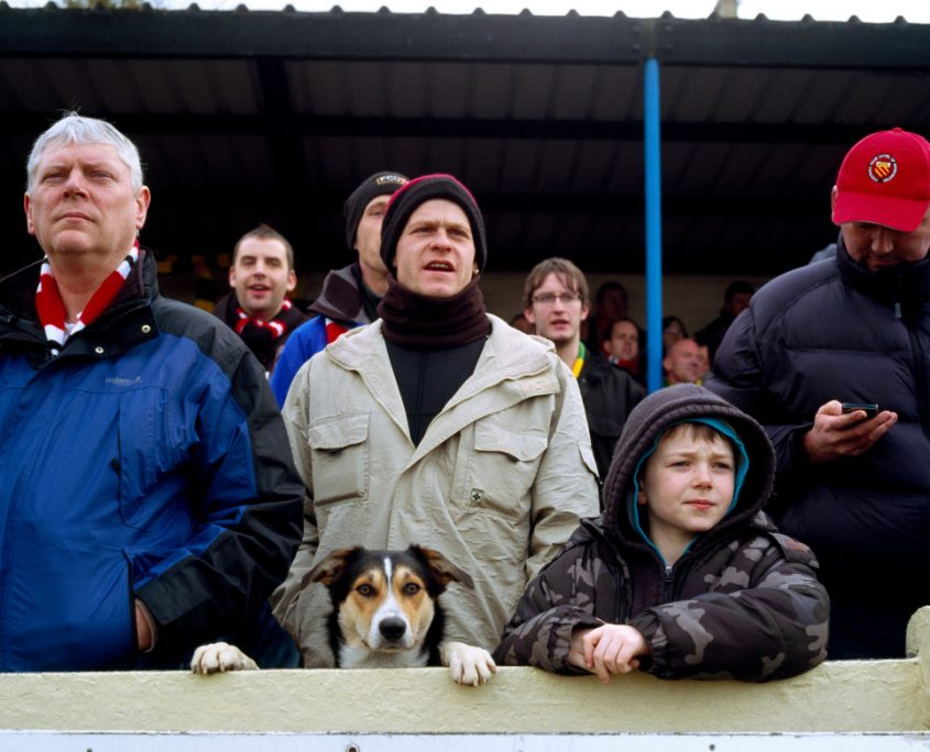 a crowd of people a dog supporting FC United of Manchester peers over the pitch perimeter at Buxton Football Club England